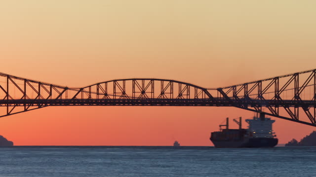 ms t/l  large boat crossing pierre laporte bridge at sunset / quebec , canada - quebec stock videos & royalty-free footage
