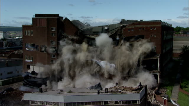 vidéos et rushes de ws large brick building is demolished in controlled implosion using explosives and dissappears in  huge cloud of dust  / newcastle upon tyne, north east england, uk - imploding