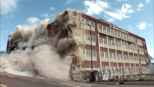 ws large brick building is demolished in controlled implosion using explosives and dissappears in  huge cloud of dust  / newcastle upon tyne, north east england, uk - 破壊点の映像素材/bロール