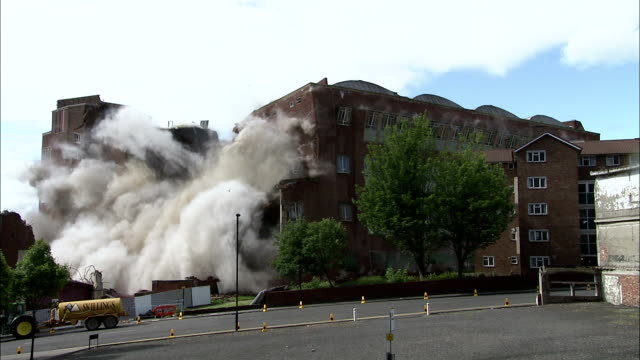 vidéos et rushes de ws large brick building is demolished in  controlled implosion using explosives / newcastle upon tyne, north east england, uk - imploding
