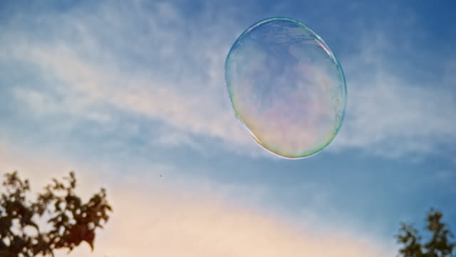 vídeos de stock e filmes b-roll de slo mo large bubble floating in the air outside with blue sky in the background - soap sud