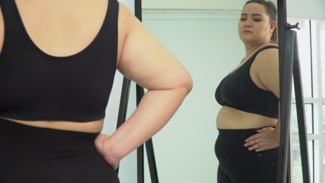 large build asian woman looking at her body in mirror - the human body stock videos & royalty-free footage