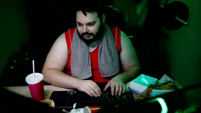 vídeos de stock e filmes b-roll de large build man playing video games - nerd