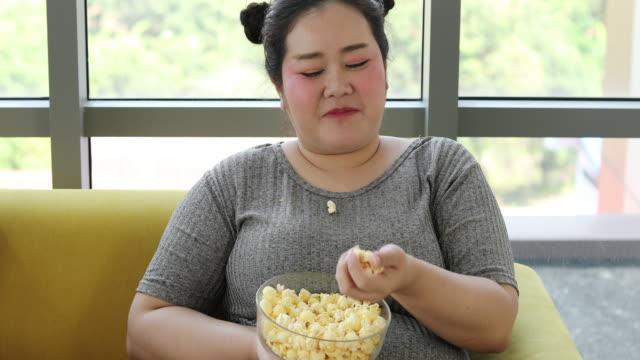 大きなビルドの女性とアジアの女の子は自宅でソファで食べ物を楽しむ - 大柄点の映像素材/bロール