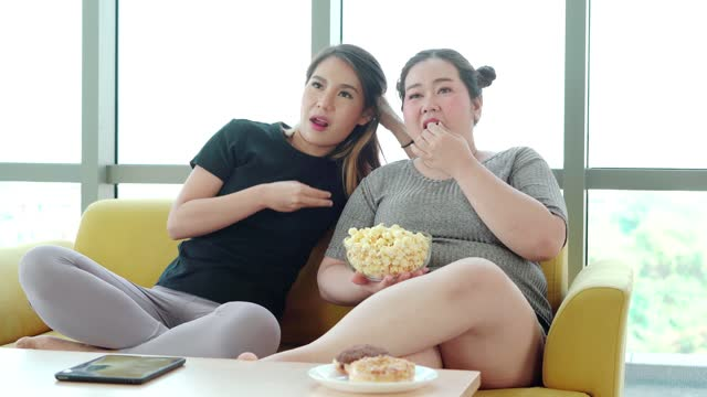 large build woman eating snack and watching television - over eating stock videos & royalty-free footage