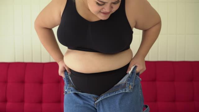 stockvideo's en b-roll-footage met grote vrouw die probeert om de knoppen van haar jeans te sluiten - nauw