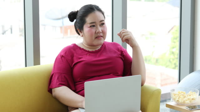 large build woman using notebook and tablet for working from home and asian girl enjoy eating food on sofa at home - large stock videos & royalty-free footage