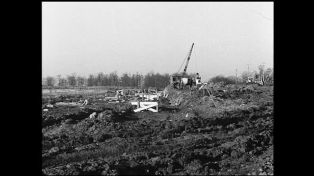 large building in construction under the cloudy sky and cars passing by; workers working on the roof; panning view of construction, crane lifting... - 1940 1949 video stock e b–roll