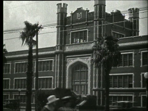 b/w large building with palm trees in front / trolley passes / 1915 new orleans / no sound - new orleans stock videos & royalty-free footage