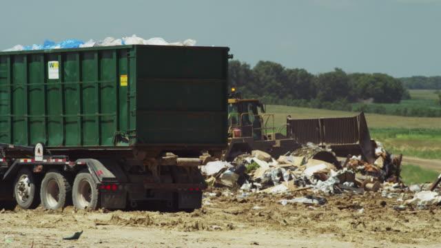 Large bulldozer at work burying waste and debris at a municipal garbage dump.