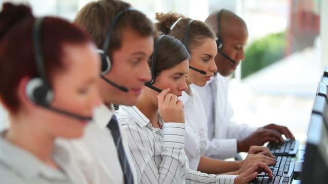 vidéos et rushes de a large business team wearing headsets - chemise et cravate