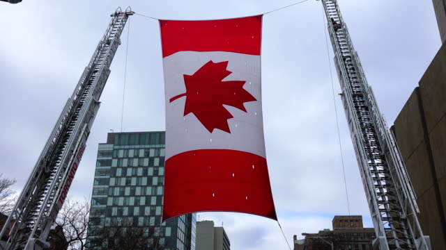 large canadian flag held between two firetrucks. the parade is also known as the feast of saint patrick is a cultural and religious celebration... - bandiera del canada video stock e b–roll