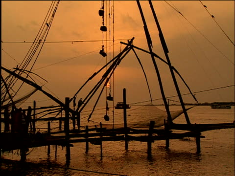 vídeos de stock e filmes b-roll de large chinese fishing net contraption is lowered into sea at sunset cochin kerala - baixar