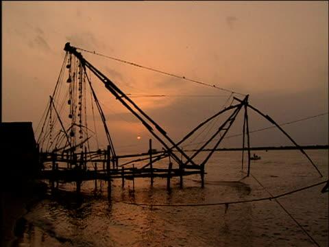 vídeos de stock e filmes b-roll de large chinese fishing net contraption is lowered into water cochin kerala - rede de pesca comercial
