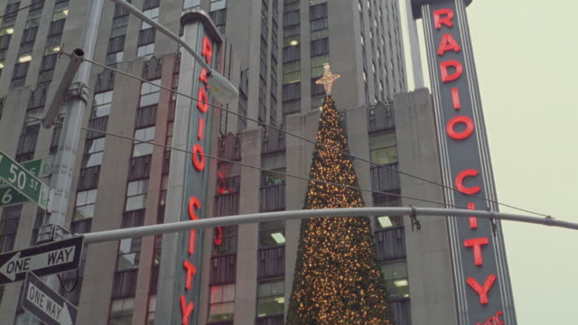 a large christmas tree and toy soldiers at the entrance of the radio city music hall. - radio city music hall stock videos & royalty-free footage