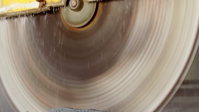 Large circular saw cuts a granite block.