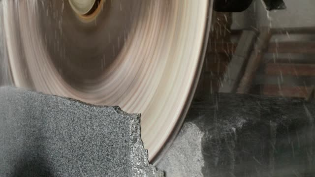 Large circular saw cuts a granite block.