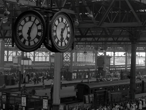 A large clock is suspended above the platforms of Waterloo Station