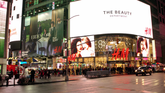 h&m large clothing retail store. illuminated billboards. times square, manhattan. tourists walking by. - commercial sign stock videos & royalty-free footage