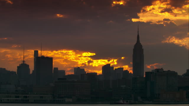 Large clouds cover sunrise above the Empire State Building and New York City skyline