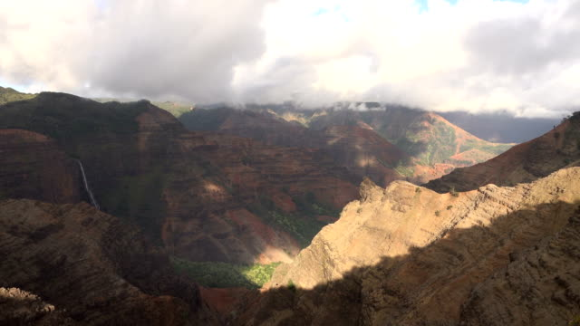 large clouds flowing over vast valley on kauai island - butte rocky outcrop stock videos & royalty-free footage
