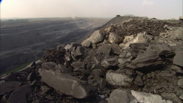 ha ws pan large coal pile on top of cliff overlooking coal landscape under hazy sky / india - heap stock videos & royalty-free footage