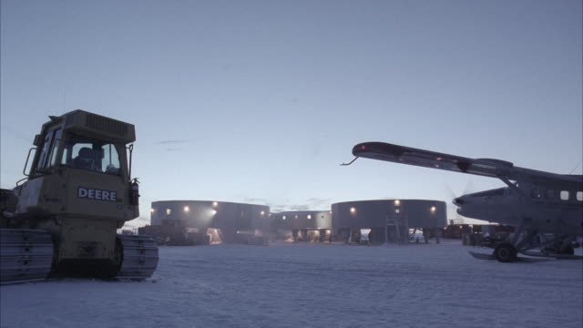 stockvideo's en b-roll-footage met ms large complex of square styled buildings, along with a large tractor like vehicle sno-cat, portion of single engine plane in ground with frozen artic landscape could work for polar weather or polar science station - onderzoeksfaciliteit