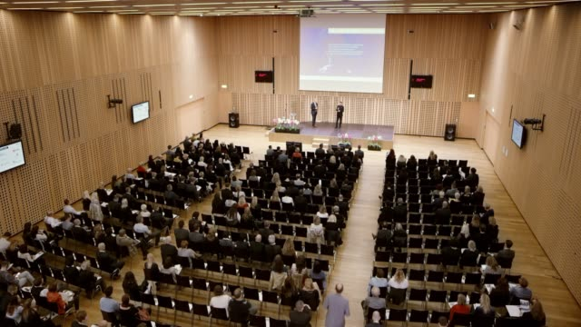 ld large conference hall with the seated seminar attendees and two speakers on the stage podium - seminar stock videos & royalty-free footage
