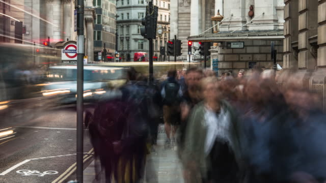 a large constant flow of city workers move rapidly along a pavement in the city of london as buses and other road traffic moves rapidly past bank tube station - central london video stock e b–roll