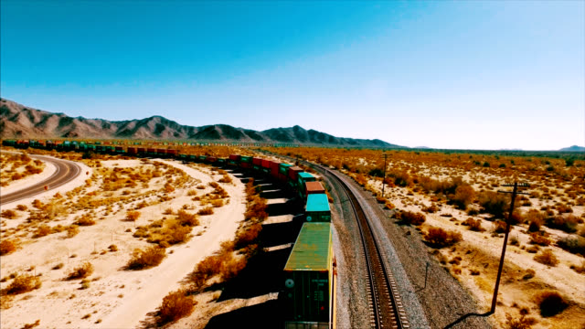 a large container locomotive travels down a railroad track in the american desert. - economy stock videos & royalty-free footage