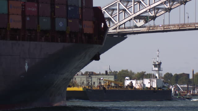 A large container ship and a barge pass each other on the Kill Van Kull waterway approaching the Bayonne Bridge.