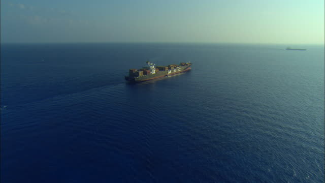 AERIAL Large container ship underway with pilot boat alongside, Freeport, Bahamas