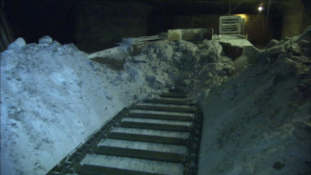 a large conveyor belt carries salt crystals to a crusher. - miniera video stock e b–roll