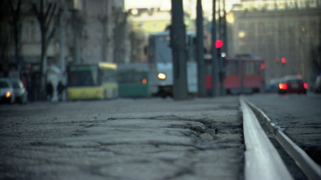 large cracks on city street lower fg out of focus trolleys coming toward frame bg traffic buildings bg of frame europe - serbia stock videos & royalty-free footage