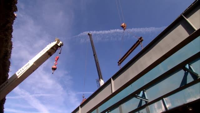 vídeos y material grabado en eventos de stock de a large crane transports i-beams above a building under construction. - grúa