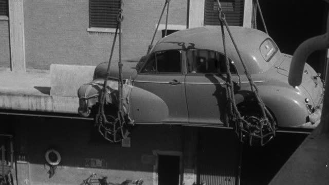 1949 montage large crane unloading cars from cargo ships at dock side, with longshoremen looking on / london, england, united kingdom - docks stock videos & royalty-free footage