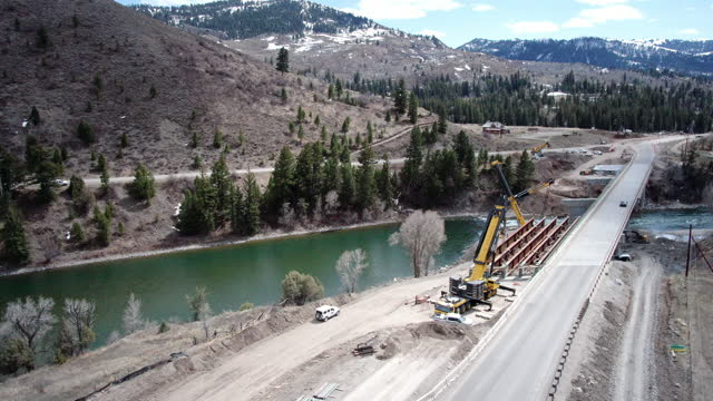 large cranes installing a bridge on a mountain road - construction vehicle stock videos & royalty-free footage