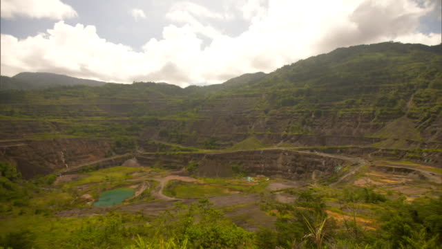 Large crater with green pond and sediment at former Panguna copper mine on Bougainville Island Papua New Guinea