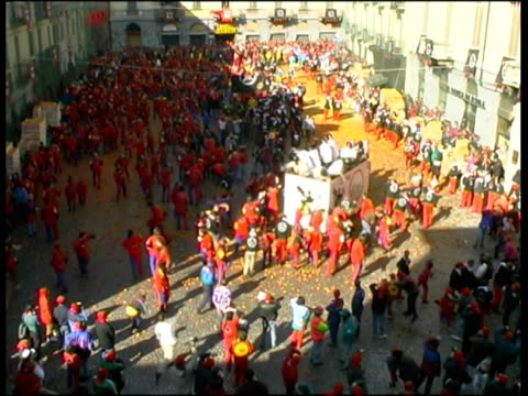 ws ha large crowd and people in horse carriage throwing oranges at each other during battle of oranges on city square / ivrea, torino, italy / audio - piemonte video stock e b–roll