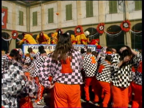 ms pan pov zi large crowd and people in horse carriage throwing oranges at each other during battle of oranges on city square / ivrea, torino, italy / audio - western script stock videos & royalty-free footage