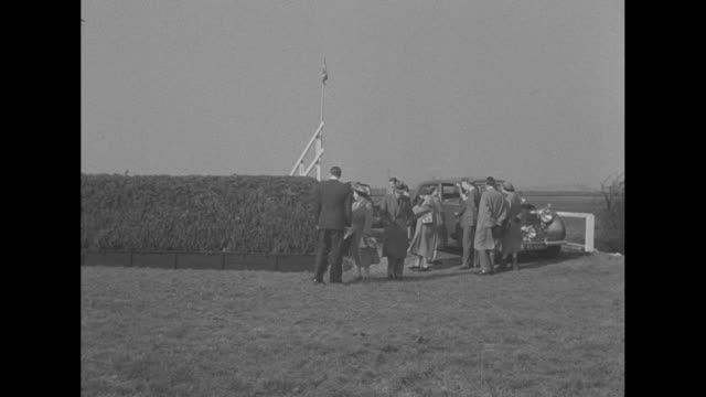 large crowd at aintree racecourse / royal standard and british flag / royal party arrives king george vi queen elizabeth princesses elizabeth and... - princess margaret 1950 stock videos and b-roll footage