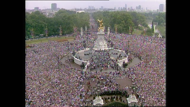 large crowd chants and sings as they wait outside buckingham palace on the day of the wedding of prince charles and lady diana spencer; 1981. - fountain stock videos & royalty-free footage
