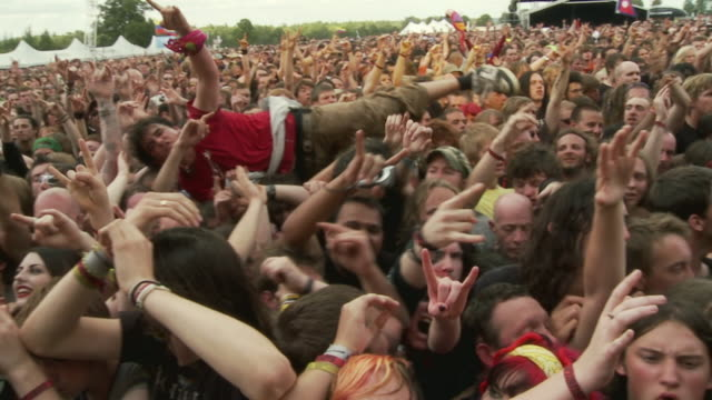 ms pan slo mo large crowd cheering at music festival, man crowd surfing and security people controlling crowd / knebworth, hertfordshire, uk - rockmusik stock-videos und b-roll-filmmaterial