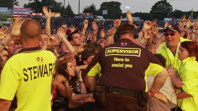 ms pan slo mo large crowd cheering at music festival, security people controlling crowd / knebworth, hertfordshire, uk  - security staff stock videos & royalty-free footage