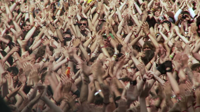 vídeos de stock, filmes e b-roll de ms slo mo large crowd clapping hands in air at music festival / knebworth, hertfordshire, uk - fã
