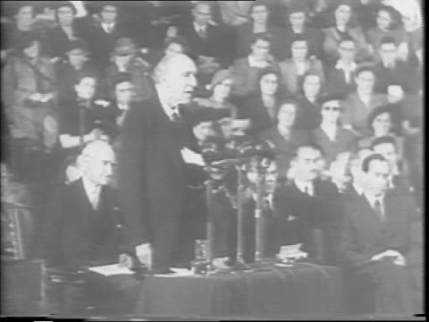 large crowd fills albert hall / lord algernon robert gascoyne cecil speaks at a podium before a bank of microphones, urging an end to war / the large... - 大量破壊兵器点の映像素材/bロール