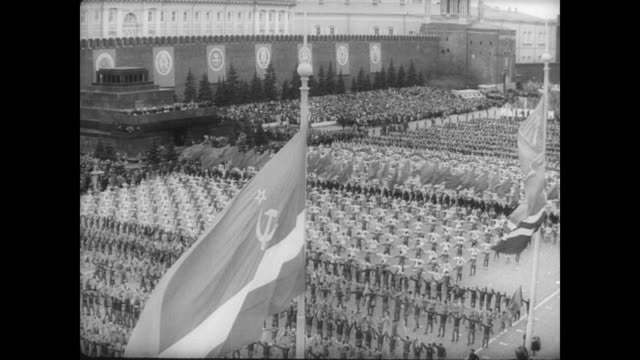 large crowd gathered in red square for moscow's may day parade / troops march in formation while giant weapons are displayed on the back of truck... - ex unione sovietica video stock e b–roll