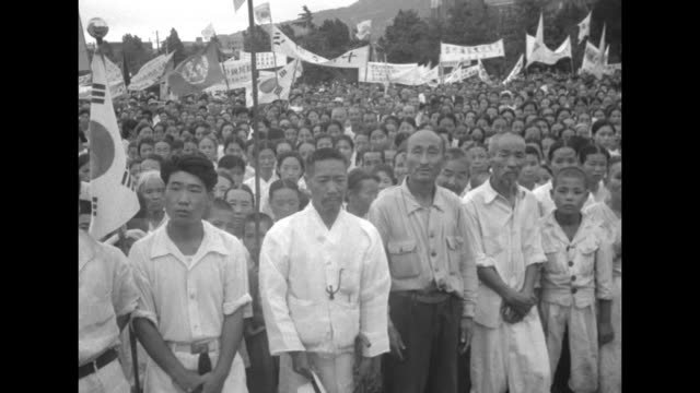large crowd holding rally, many in crowd holding banners / four shots of people marching / note: exact month/day not known - korean war stock videos & royalty-free footage