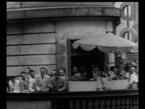 ws large crowd in buenos aires / people in crowd hold banners featuring juan peron's likeness and name / men on balcony with microphone / ws crowd /... - 表す点の映像素材/bロール