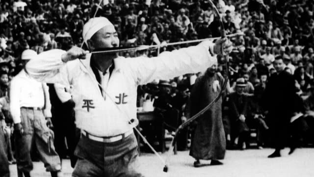 vidéos et rushes de large crowd in stadium waving flags / row of chinese athletes holding ancient sports paraphernalia / man demonstrates traditional archery / cu straw... - 1933